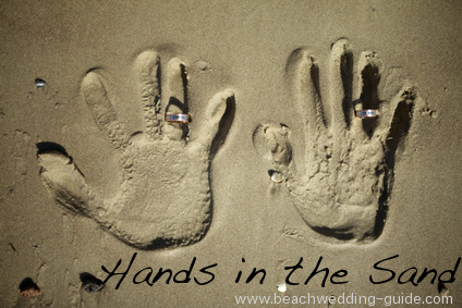 beach wedding hands in the sand