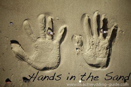 beach wedding hands in the sand